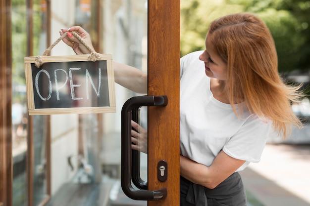 Mujer sosteniendo somos señal abierta Foto gratis