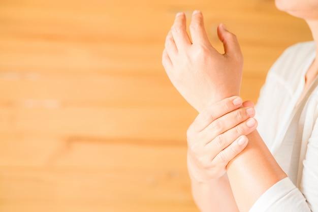 Mujer sosteniendo su muñeca síndrome de office sintomático Foto gratis