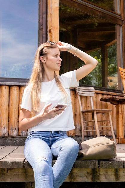 Mujer sosteniendo sus gafas de sol y mirando a otro lado Foto gratis