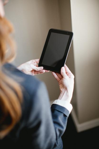 Mujer sosteniendo tablet o smartphone con manos, pantalla negra Foto gratis