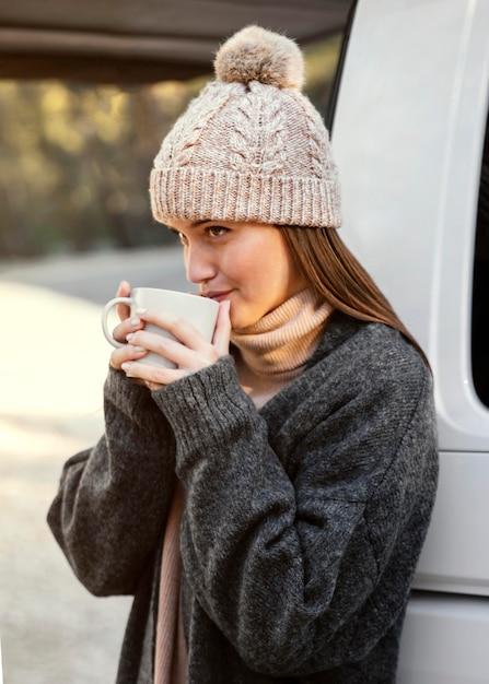 Mujer sosteniendo una taza de tiro medio Foto gratis