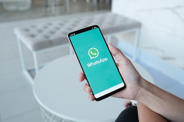 Mujer sosteniendo un teléfono inteligente y abrir la tienda de aplicaciones buscando servicio de internet social whatsapp en la pantalla. Foto Premium