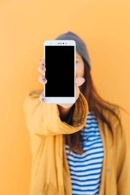 Mujer sosteniendo un teléfono móvil con pantalla en blanco de pie delante de telón de fondo amarillo Foto gratis