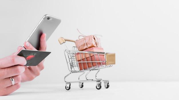 Mujer sosteniendo teléfono y tarjeta de crédito Foto gratis