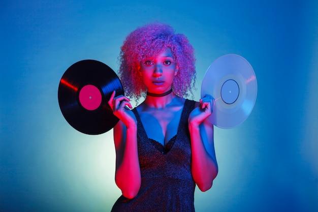 Mujer sosteniendo viejos vinilos de música en coloridas luces de neón Foto Premium