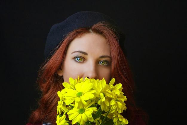 La mujer sostiene un crisantemo amarillo Foto Premium