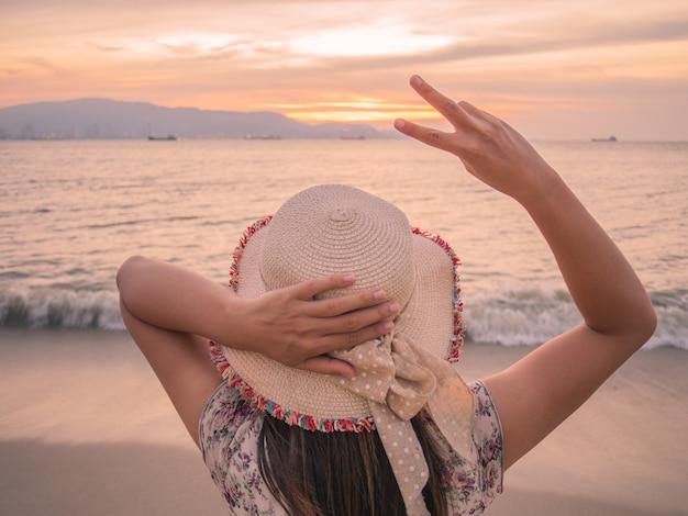 La mujer sostiene dos dedos o muestra de la victoria en la playa durante puesta del sol Foto Premium