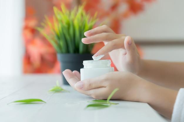 Mujer sostiene un frasco con una crema cosmética en sus manos Foto gratis
