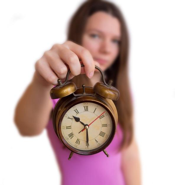 La mujer sostiene un reloj de alarma sobre un fondo blanco. cambio de horario a invierno o verano Foto Premium