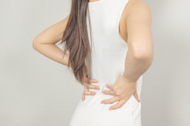 Una mujer sostuvo su mano detrás de él con dolor de espalda. concepto de salud Foto Premium