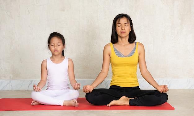 Mujer y su encantadora hijita haciendo yoga Foto gratis