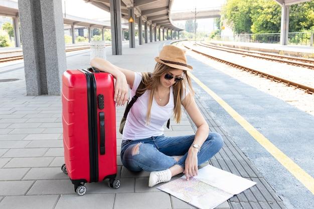 Mujer y su equipaje mirando un mapa Foto gratis