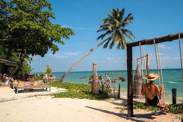 Mujer en su escapada romántica de luna de miel aislada en una playa paradisíaca con palmeras. caro resort de lujo para parejas casadas y solteros. relájate en un columpio. viaje al concepto de tailandia. Foto Premium
