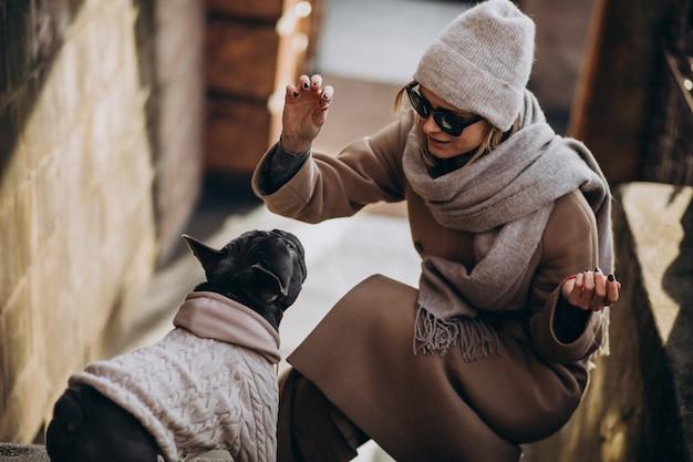 Mujer con su mascota bulldog francés saliendo Foto gratis