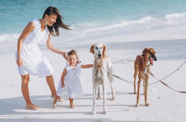 Mujer con su pequeña hija jugando con perros en la playa junto al mar Foto gratis