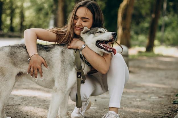Mujer con su perro husky en el parque Foto gratis
