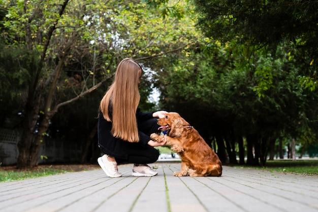Mujer con su perro en el parque Foto gratis