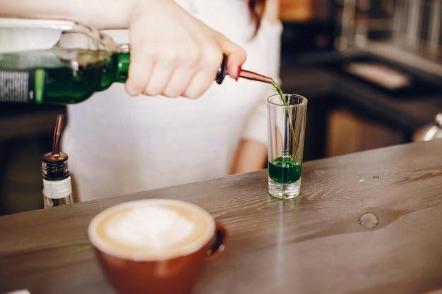 Mujer en un suéter blanco vertiendo syrop verde en vidrio Foto gratis
