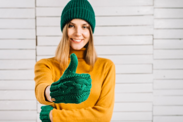 Mujer en suéter que muestra el pulgar hacia arriba Foto gratis