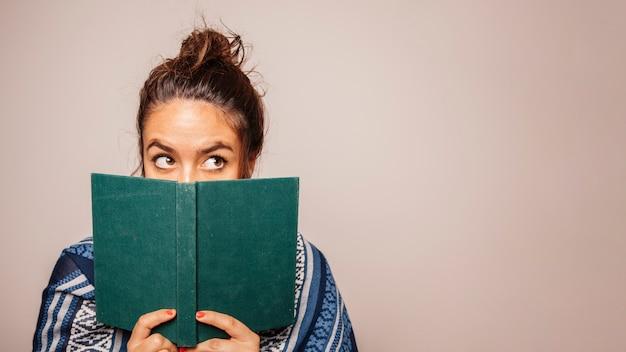 Mujer sujetando libro enfrente de cara Foto gratis