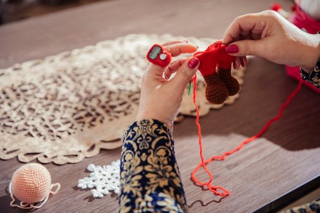 Mujer tejiendo figuras con hilo rojo Foto gratis