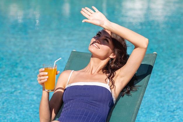 Mujer tendida en el salón bloqueando el sol con la mano Foto gratis