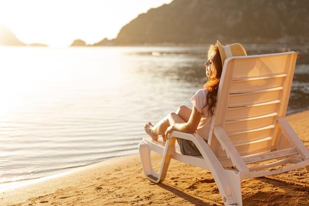 Mujer tendida en el salón mirando al mar Foto gratis