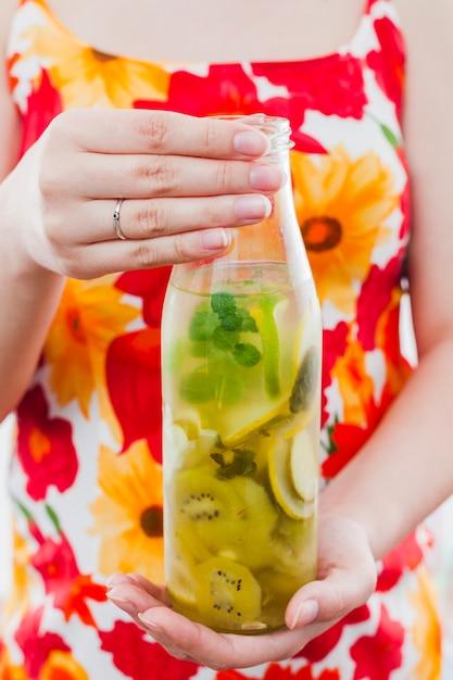 Mujer, tenencia, botella, de, fruta, bebida Foto gratis