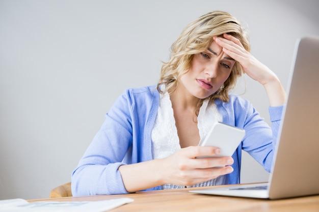 Mujer tensionada que usa el teléfono móvil Foto gratis