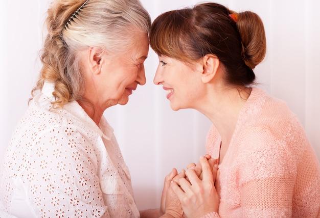 Mujer de la tercera edad con su cuidador en casa Foto Premium