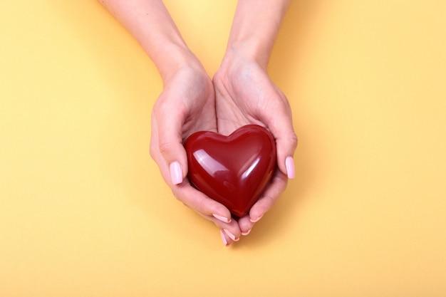 Una mujer tiene un corazón rojo en sus manos. Foto Premium