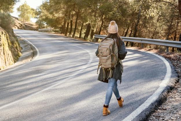 Mujer de tiro completo caminando por la carretera Foto gratis