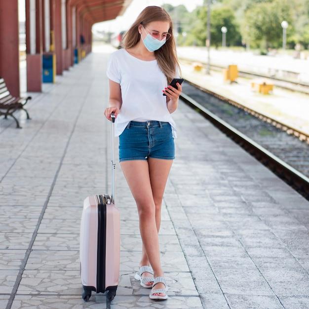 Mujer de tiro completo con equipaje en la estación de tren Foto gratis