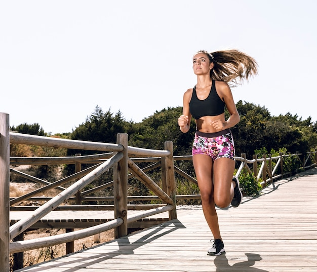 Mujer de tiro largo corriendo en el muelle Foto gratis