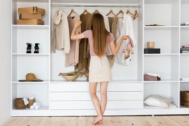 Mujer de tiro largo mirando a través de su ropa Foto gratis