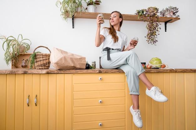 Mujer de tiro largo posando sobre una encimera de cocina Foto gratis