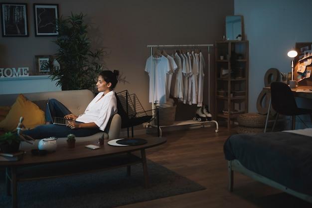 Mujer de tiro largo que trabaja en la computadora portátil desde casa Foto gratis