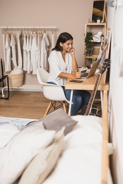 Mujer de tiro largo trabajando desde casa Foto gratis