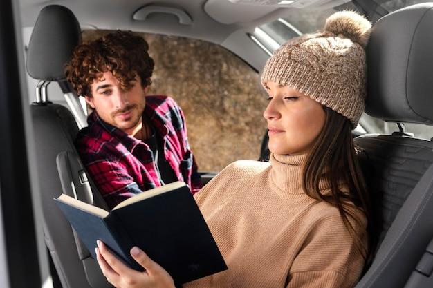 Mujer de tiro medio leyendo en coche Foto gratis