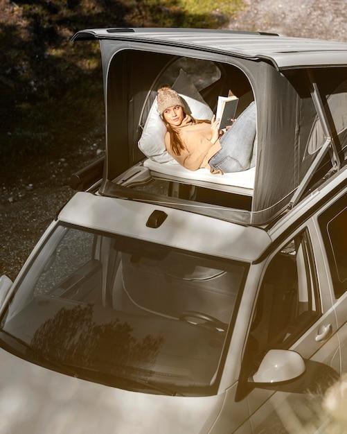 Mujer de tiro medio con libro durante el viaje por carretera Foto Premium