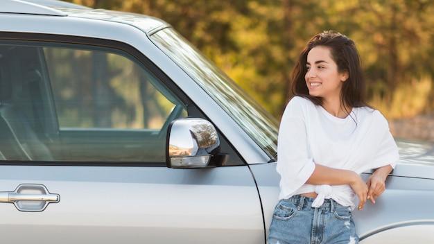 Mujer de tiro medio posando cerca del coche Foto gratis
