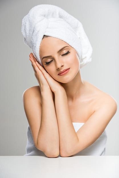 Mujer con una toalla en la cabeza, cerrando los ojos. Foto Premium