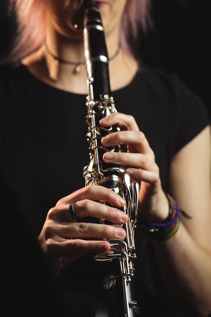 Mujer tocando un clarinete en la escuela de música Foto gratis