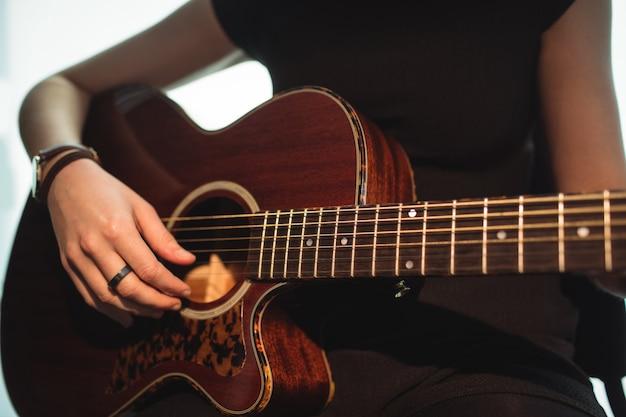 Mujer tocando una guitarra en la escuela de música Foto gratis