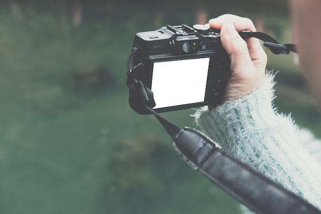 La mujer toma la foto del estanque tranquilo verde en el parque. Foto Premium