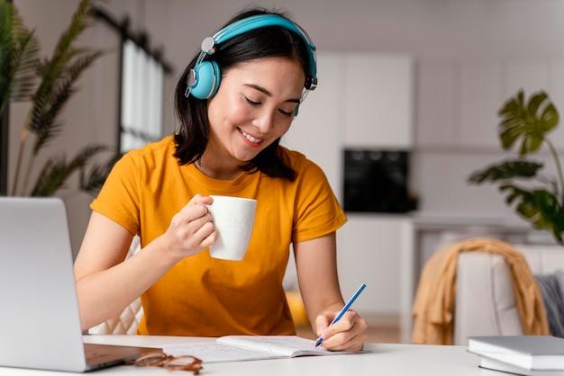 Mujer tomando café mientras asistía a clases online Foto gratis