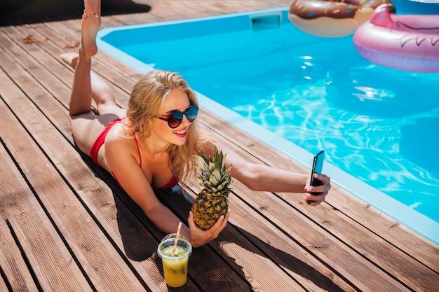 Mujer tomando un selfie con una piña Foto gratis