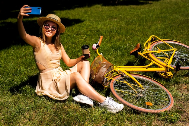 Mujer tomando una selfie con su bicicleta Foto gratis
