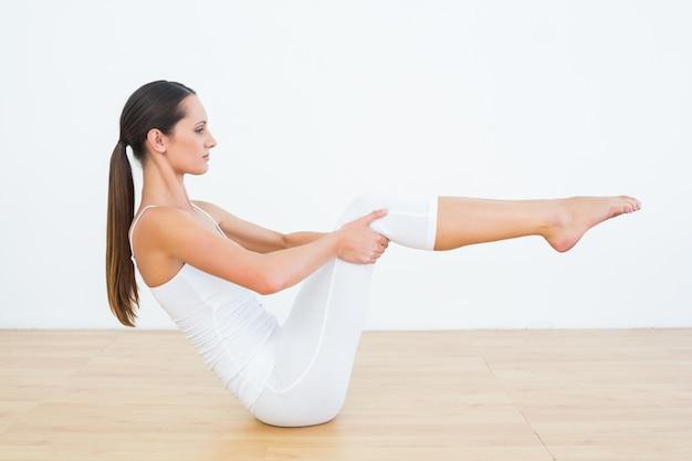 Mujer tonificada haciendo la pose del barco en el gimnasio