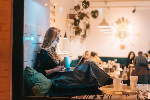 Mujer trabaja en un café en la noche Foto gratis